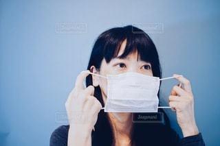 マスクを取ろうとする女性の写真・画像素材[3330274]