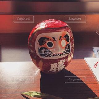 木製のテーブルの上に座るだるまの写真・画像素材[2206184]