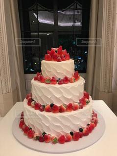テーブルの上に座っている大きな白いケーキの写真・画像素材[2204853]