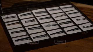 木製のテーブルの上に陳列されたネクタイピンの写真・画像素材[2343713]
