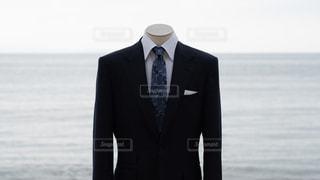水の体の前に立つ濡れたスーツを着た男の写真・画像素材[2343725]
