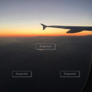 オレンジ色の夕日に乗った大きな飛行機の写真・画像素材[2228021]