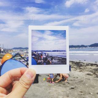 砂浜でチェキの写真を持っての写真・画像素材[1293509]