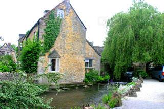石造りの建物の前の茂みのある家と川面の写真・画像素材[2230506]