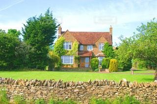 芝生のある赤い屋根と煙突の家の写真・画像素材[2230887]