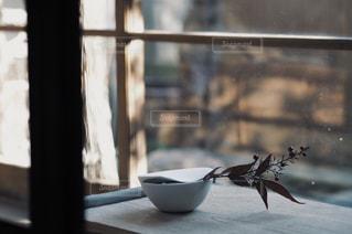 窓の前に座っている花瓶の写真・画像素材[2233633]