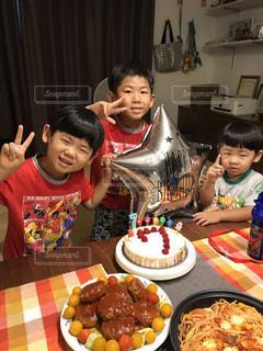 食べ物の皿を持ってテーブルに座っている小さな女の子の写真・画像素材[2264989]