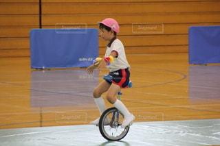 自転車の後ろに乗っている小さな女の子の写真・画像素材[2681310]