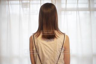 カーテンの前に立つ女性の写真・画像素材[2287082]