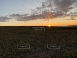夕焼けの前に立っている男の写真・画像素材[2447363]
