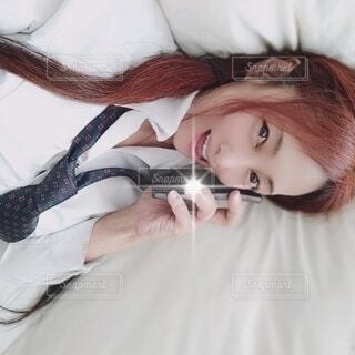 寝転んで笑顔で電話をする女性の写真・画像素材[4542275]