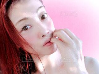 桃色背景と女性の顔のクローズアップの写真・画像素材[4704086]