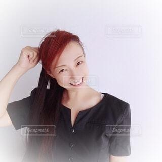 嬉しくて照れ笑いをする女性の写真・画像素材[4704953]