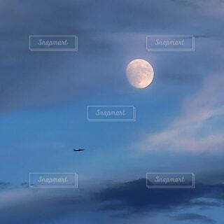 夜空に輝く月と飛行機の影の写真・画像素材[4738149]