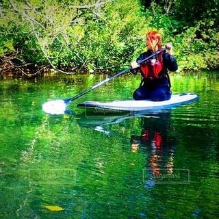 綺麗な水の上でボードに乗る女性の写真・画像素材[4770862]