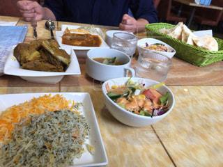 食べ物の皿を持ってテーブルに座っている女性の写真・画像素材[2454029]