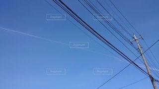 澄んだ青空 飛行機雲 電線の写真・画像素材[3011551]