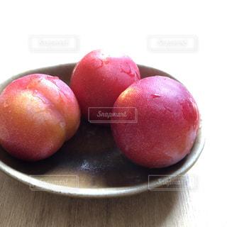 お皿の上の3つのプラムの写真・画像素材[2270339]