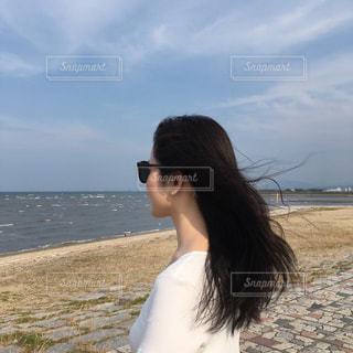 水域の近くの浜辺に立っている人の写真・画像素材[2295681]