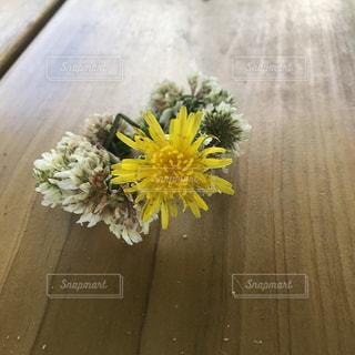 木製のテーブルの上に座っている花飾りの写真・画像素材[2295992]