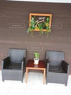 レンガの壁の前に座っている椅子の写真・画像素材[2312300]