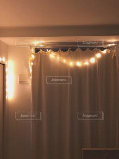 カーテンの前に立っている人の写真・画像素材[2303743]