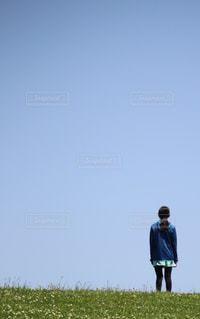 丘の上に立つ少女の写真・画像素材[2322739]