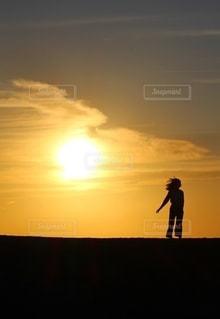 太陽と少女のシルエットの写真・画像素材[2642202]