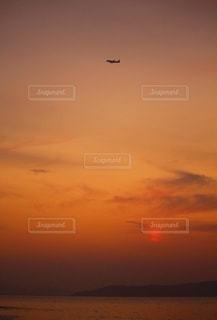 夕暮れ時を飛ぶ飛行機の写真・画像素材[2684877]