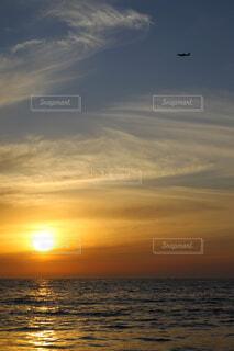 夕陽の空に飛行機の写真・画像素材[4464161]