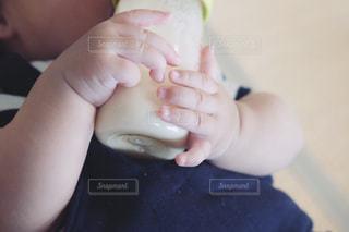 哺乳瓶を持つ手の写真・画像素材[2318612]