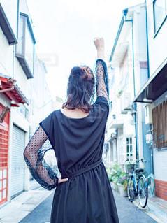 道で拳を上げる女性の後ろ姿の写真・画像素材[2505047]