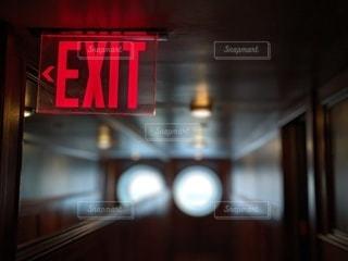 暗い廊下に光るEXITサインの写真・画像素材[2435914]