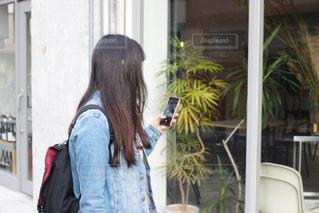 ウィンドウの前に立っている女性の写真・画像素材[1591802]