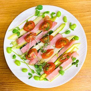 テーブルの上に異なる種類の食べ物をトッピングした白い皿の写真・画像素材[2333026]