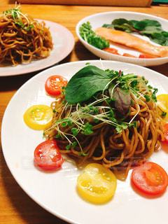 テーブルの上に異なる種類の食べ物をトッピングした白い皿の写真・画像素材[2333119]
