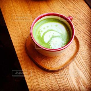 木製のテーブルの上に座っているコーヒー1杯の写真・画像素材[2380453]