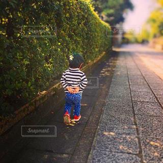 歩道を歩く小さな女の子の写真・画像素材[2381330]