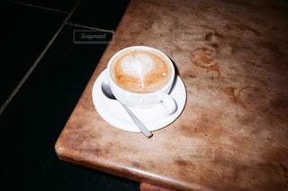 木製のテーブルの上に座っているコーヒー1杯の写真・画像素材[2375712]