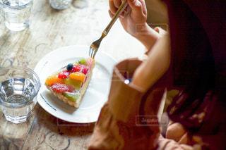 食べ物の皿を持ってテーブルに座っている人の写真・画像素材[2959359]