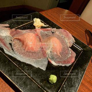 木製のまな板の上に座っている食べ物の皿の写真・画像素材[2354981]