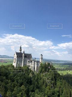 ノイシュヴァンシュタイン城を背景にした建物のような城の写真・画像素材[2347294]