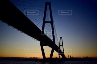夕焼けを背景にした水域に架かる橋の写真・画像素材[2370712]