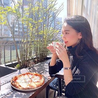 ピザを食べるテーブルに座っている女性の写真・画像素材[3224033]