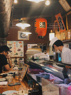 店の前のテーブルに座っている男の写真・画像素材[2351774]