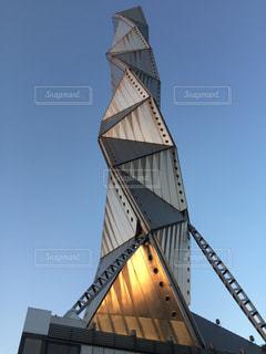 建物の側に時計と大きな背の高い塔の写真・画像素材[1051591]