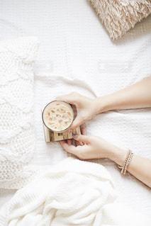 ベッドの上でくつろぎながらコーヒーの写真・画像素材[2497851]