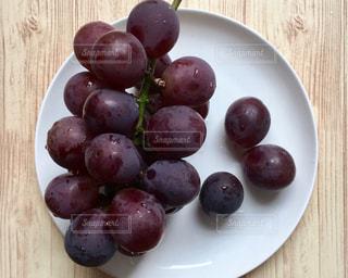 木製のテーブルの上に座っている果物のボウルの写真・画像素材[2552733]