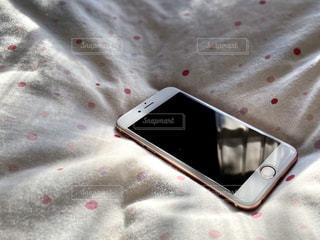 ベッド上の携帯電話のクローズアップの写真・画像素材[2824136]