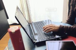 テーブルの上に座っているラップトップコンピュータを使っている人の写真・画像素材[3139713]